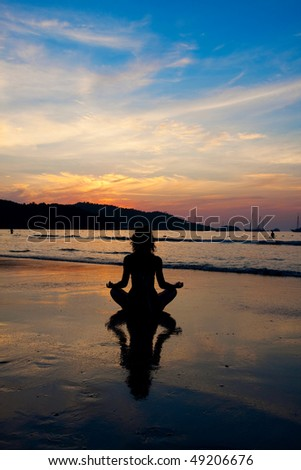 Silhouette of a woman meditating by the sea - stock photo