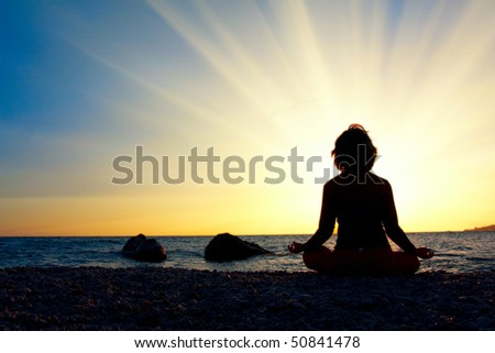 Silhouette of a woman meditating by the sea