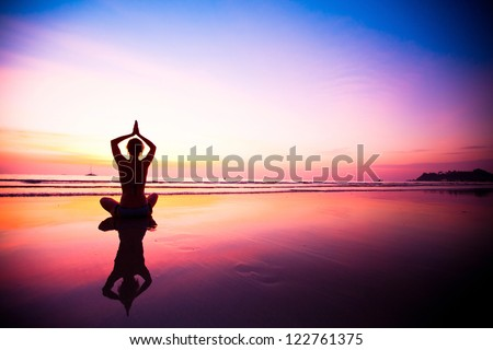 Silhouette of a woman meditating on the beach at sunset - stock photo