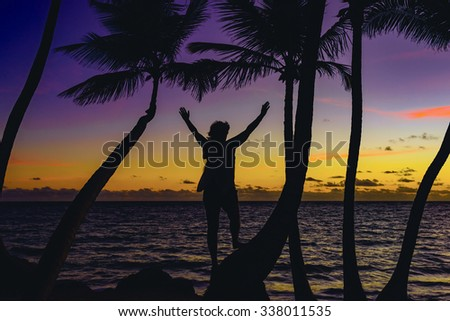 silhouette of a woman meets sunrise on the beach background palm trees