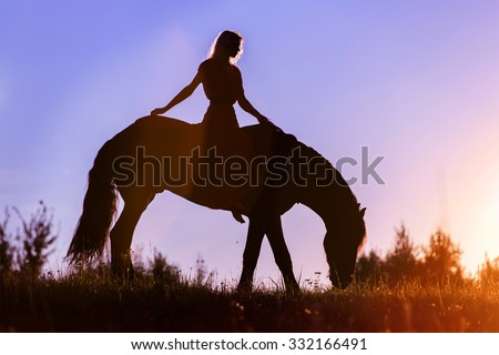 Silhouette of a woman on a horse. - stock photo