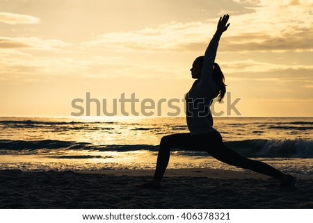 Silhouette of a woman on the beach during morning exercises at sunrise - stock photo