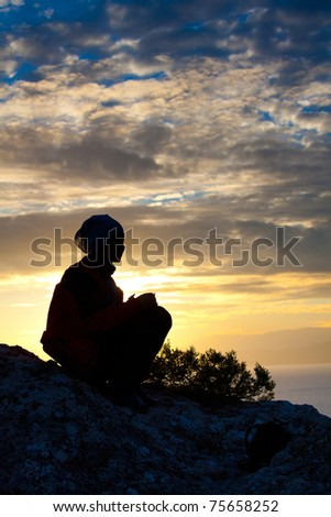 Silhouette of a woman on top of the mountain at the sea while sunset