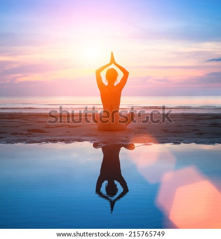 Silhouette of a woman practicing yoga on the beach with reflection in water and in the glow of an amazing sunset.