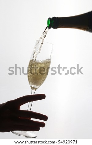 silhouette of a woman's hand holding a champagne glass, in that champagne is poured