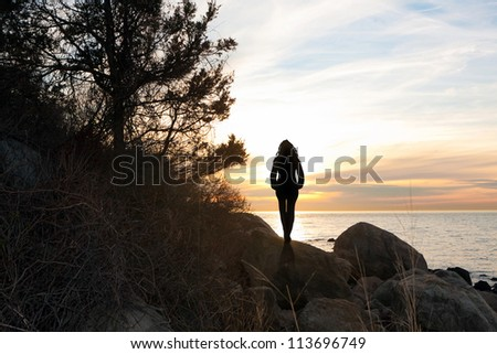 Silhouette of a woman standing in front of the sunset at the New England shoreline. - stock photo