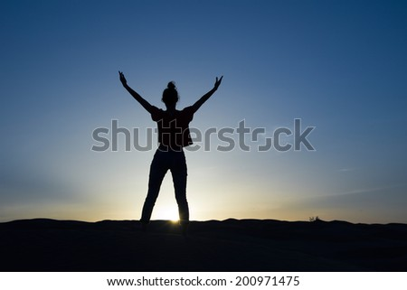 Silhouette of a woman standing in the sunlight with the arms up - stock photo