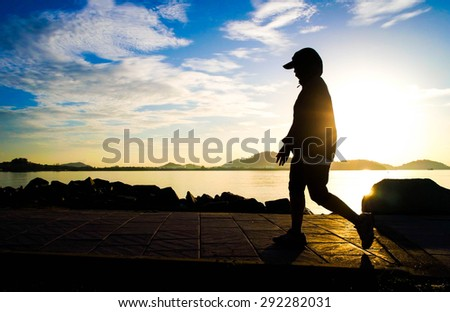 Silhouette of a woman walking for exercise in park