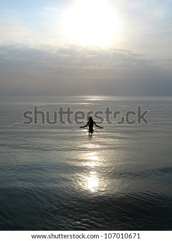 silhouette of a woman walking into a sea