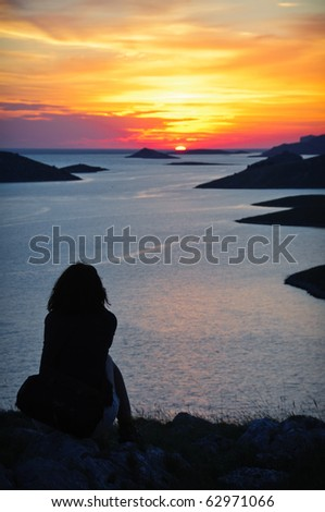 Silhouette of a woman watching golden sunset over sea - stock photo