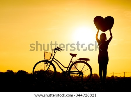 Silhouette of a woman with a bicycle and holding big hearts  - stock photo