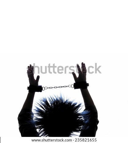 Silhouette of a woman with blue hair  in handcuffs pleading with arms aloft - stock photo