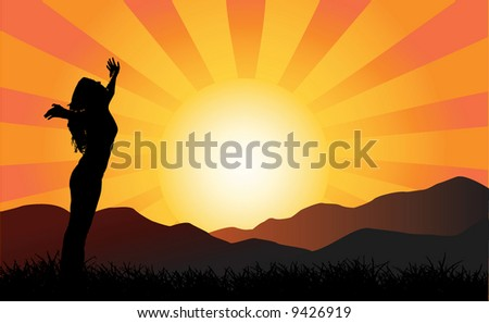 Silhouette of a woman with her arms in the air at sunset