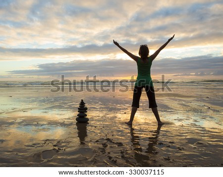 Silhouette of a woman with open arms at the beach close to a stones pile - stock photo
