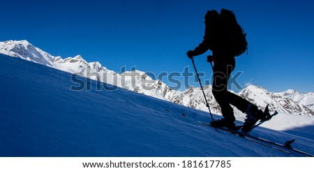 Silhouette of a woman with ski in winter mountains