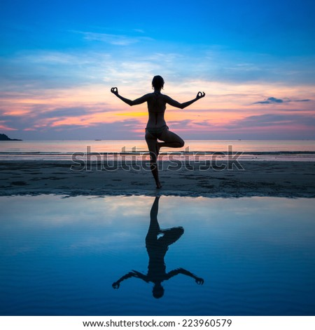 Silhouette of a woman yoga at sunset on the ocean beach with reflection in water. - stock photo