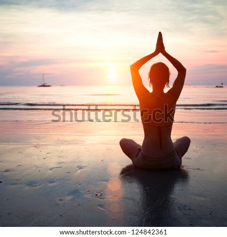 Silhouette of a woman yoga on sea sunset. - stock photo