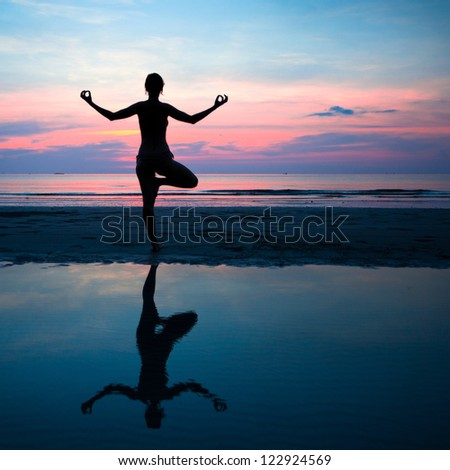 Silhouette of a woman yoga on sea sunset with reflection in water. - stock photo