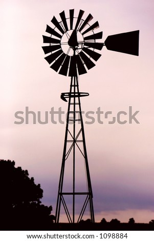 Silhouette of a working vintage country Windmill in sunset light or twilight. - stock photo