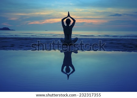 Silhouette of a yoga girl on sea beach after sunset with reflection in water. Old polar style. - stock photo
