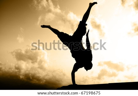 Silhouette of a young acrobatic man standing on one hand with the sky in background. - stock photo