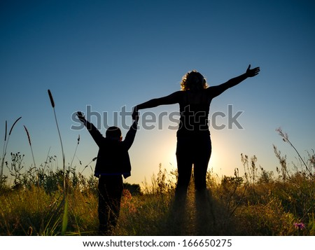 Silhouette of a young boy and his mother in the field in summer