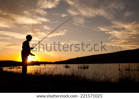 Silhouette of a young boy fly fishing at sunset - stock photo