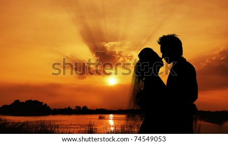 silhouette of a young bride and groom on Sunset background