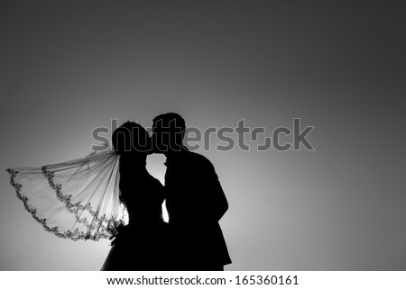 silhouette of a young bride and groom on Sunset background black and white - stock photo