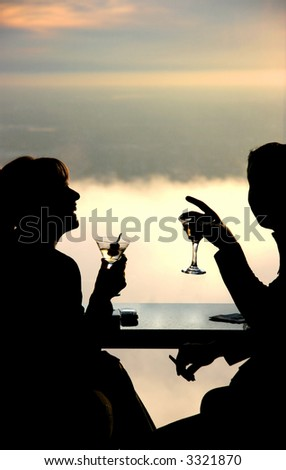 Silhouette of a young couple drinking and having fun. Top floor skyscraper lounge window at sunset - stock photo