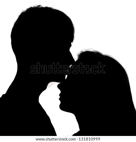 Silhouette of a young couple in love. A man kissing a girl on the forehead. Isolated on white background