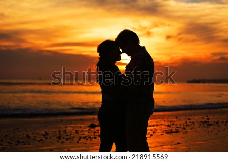 Silhouette of a young couple kissing at the beach with the sun  - stock photo