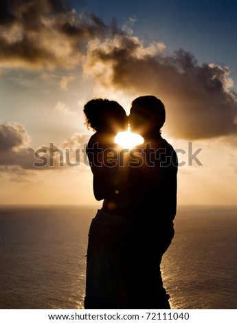 Silhouette of a young couple kissing at the beach with the sun setting behind them - stock photo