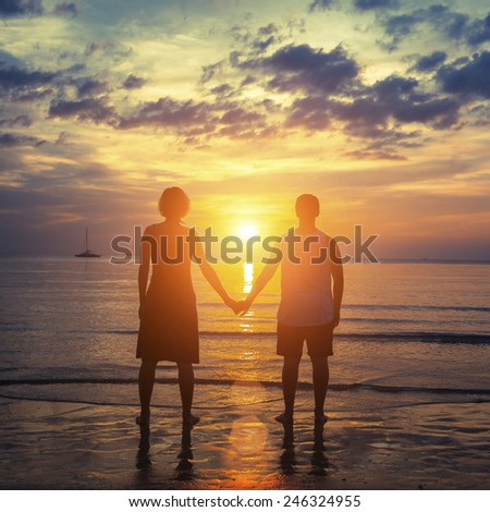 Silhouette of a young couple on their honeymoon standing on the ocean beach at amazing sunset. - stock photo