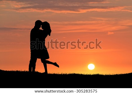 Silhouette of a young couple. Sunset background. - stock photo