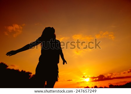 Silhouette of a young girl at sunset - stock photo