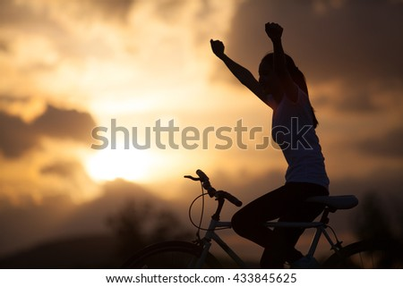 Silhouette of a young girl on mountain bike - stock photo