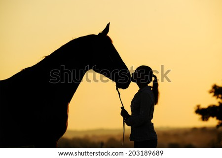 Silhouette of a young  girl with horse giving him a kiss at the sunset  - stock photo