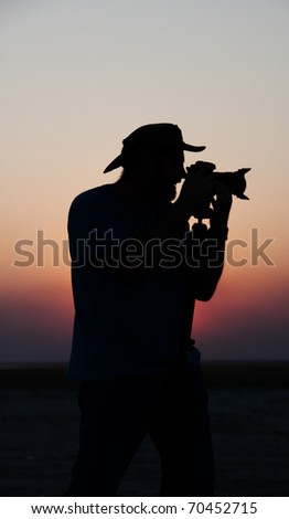 Silhouette of a young man in a hat taking pictures at sunset using a tripod - stock photo