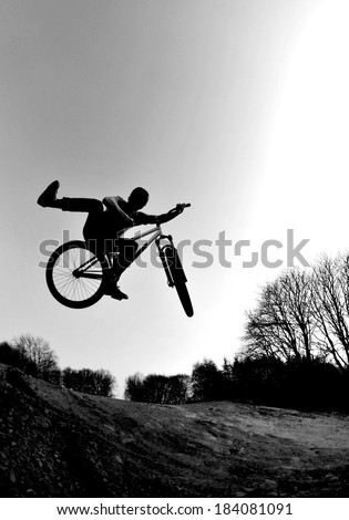 Silhouette of a young man performing a radical bmx jump