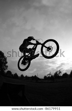 Silhouette of a young man performing a radical mountain bike jump - stock photo