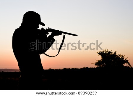 Silhouette of a young man shooting - stock photo