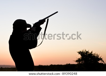 Silhouette of a young man shooting with a long rifle against sunset sky - stock photo