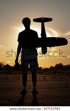 Silhouette of a young man with a model rc airplane against sunset sky