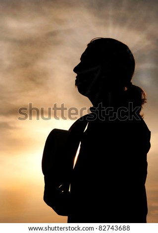 Silhouette of a young man with a ponytail gazing towards sky, holding his cowboy hat against his chest - stock photo