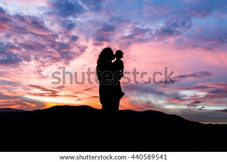 Silhouette of a young mother lovingly kissing her little child front of a sunset - stock photo