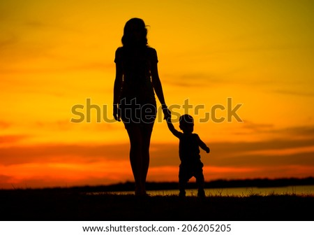 Silhouette of a young mother with her little child - stock photo