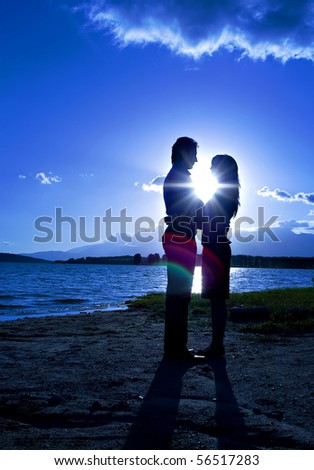 Silhouette of a young romantic couple looking at each other at the beach with the sun setting behind them