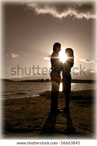 Silhouette of a young romantic couple looking at each other at the beach with the sun setting behind them - stock photo