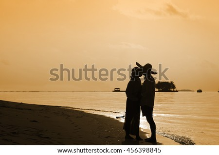Silhouette of a young romantic couple on sunset